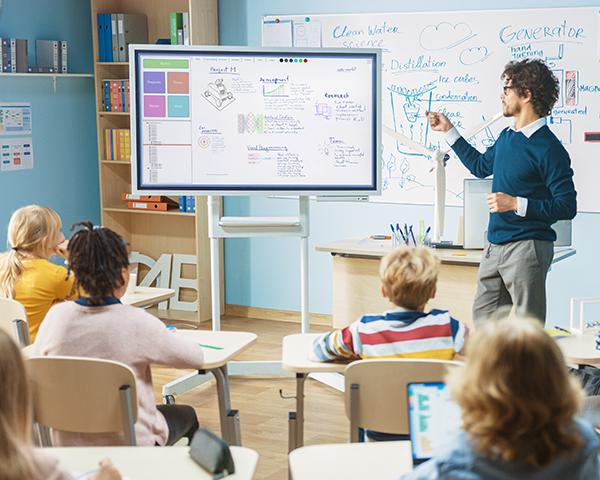 K-12 teacher using interactive whiteboard for students